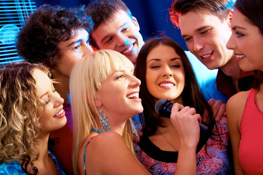Image of happy young woman sings a song in the environment of her friends