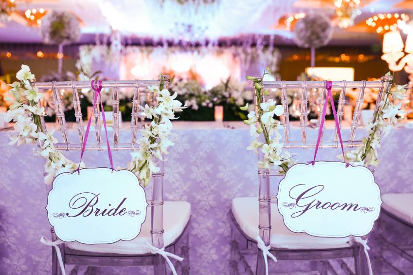 Close up DSLR pictures of bride and groom chair from back view. There's a note that show bride and groom chair on the paper tied by a purple ribbon. The table cloth has a floral pattern. The chair decorated by a flower. The background is a blurred showing the flower arrangements.