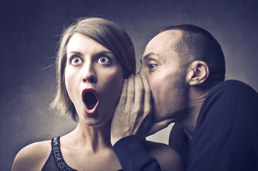 Man telling a secret to an astonished woman